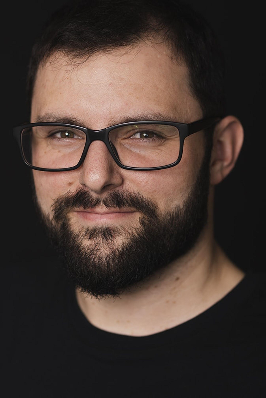 Headshot of Matthew Basile with a dark background.